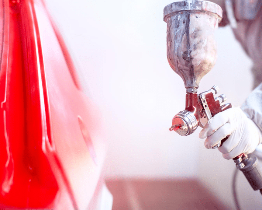 auto body painter is painting the car with red car paint