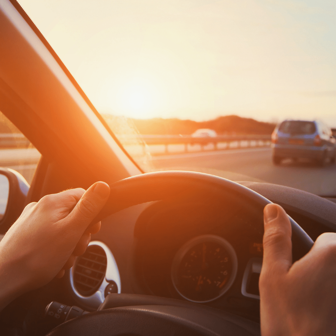 visual image of hands on steering wheel, driving on highway during sunset